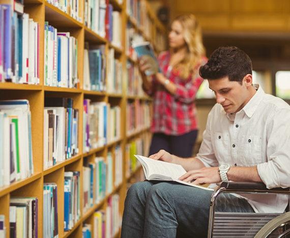 Chico en silla de ruedas leyendo un libro en la biblioteca frente a la estantería